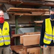 2 Männer mit angezogenen gelben Westen stehen in der Tischlerei des Lebenshilfewerk Pinneberg