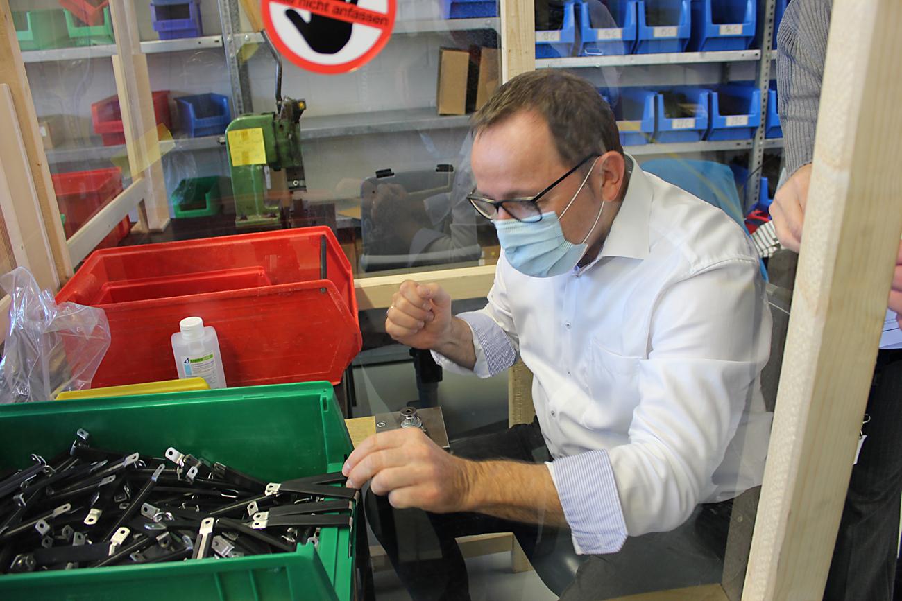 Herr Behrens darf in der Werkstatt Schellen drehen