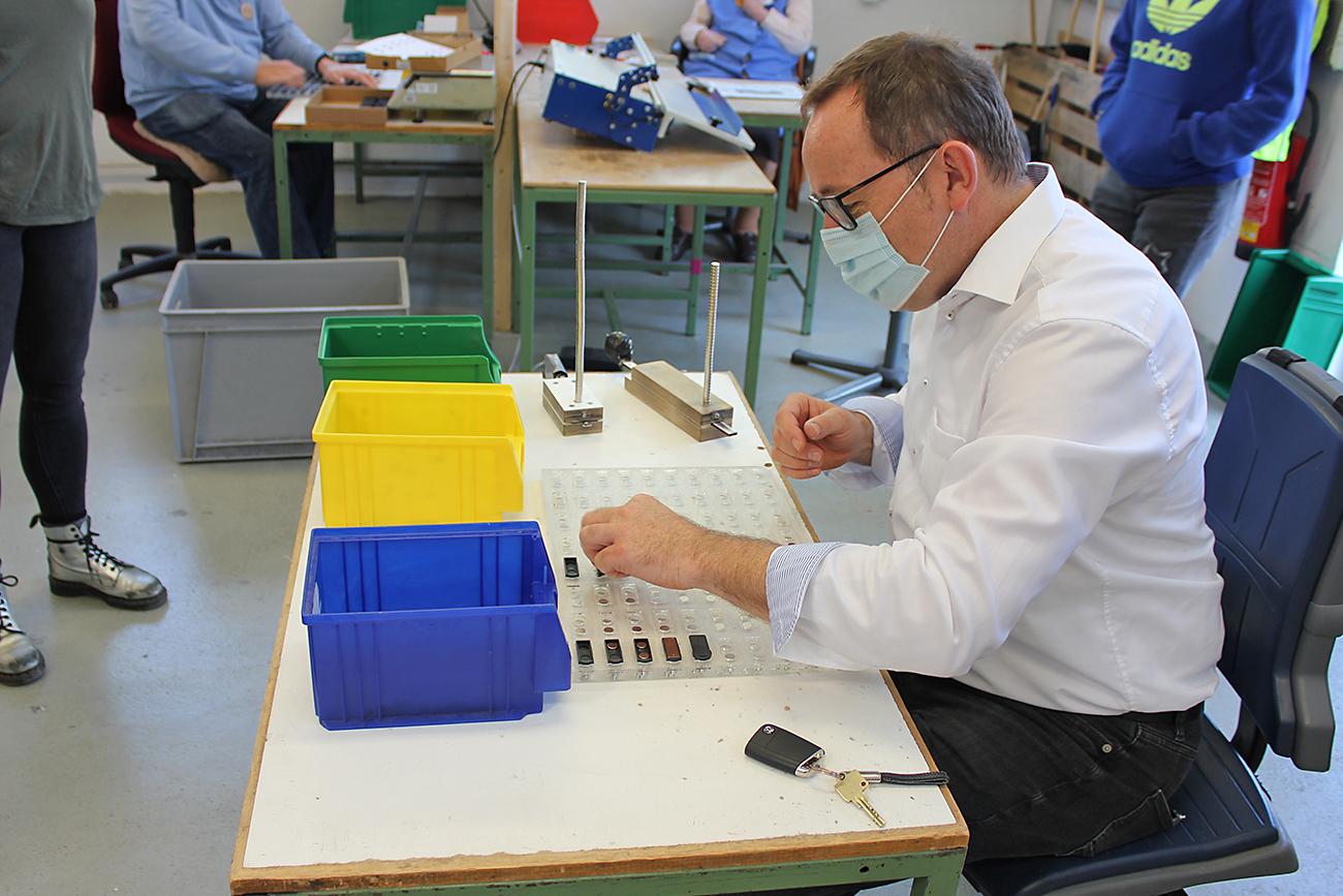 Herr Behrens darf in der Werkstatt Magnetschilder zusammenbauen