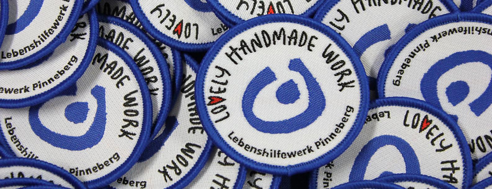 """Viele Aufnäher mit dem Schriftzug """"Lovely Handmade Work"""", das Logo der Eigenmarke des Lebenshilfewerk Pinneberg"""